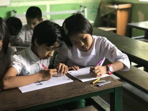 Students from a new program school in Mandalay, Myanmar participate in a baseline knowledge test.