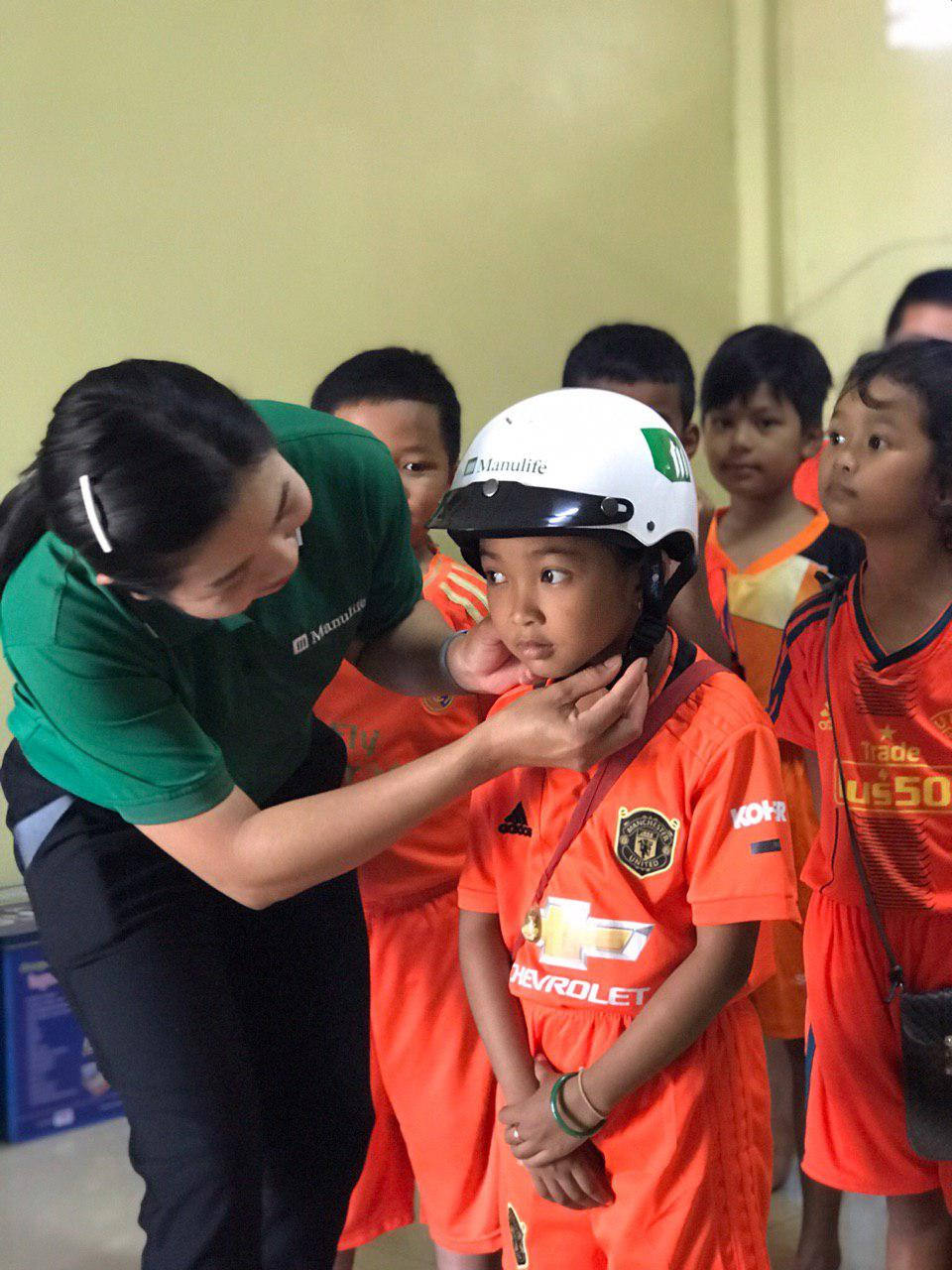 Manulife Cambodia volunteer helps student with helmet fitting.