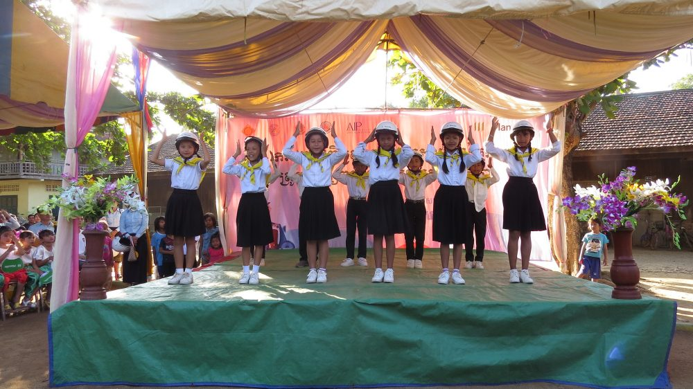 Students participating in a performance with their brand new helmets on stage.
